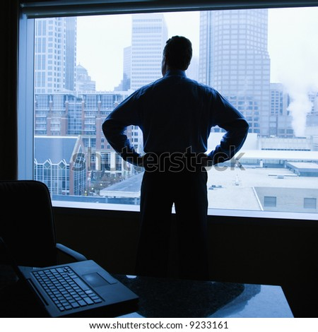 Middle-aged Caucasian male with hands on his hips in office with skyline in background. - stock photo
