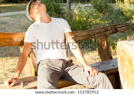 Middle-aged Caucasian man experiencing hallucinations after a drug dose administered intravenously on a bench in the park - stock photo