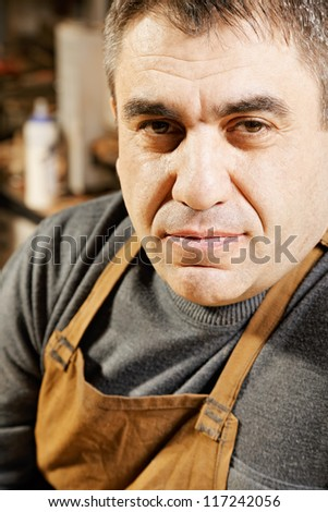 Middle-aged caucasian man in apron closeup photo - stock photo