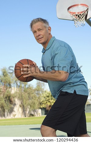 Middle aged Caucasian man playing basketball - stock photo