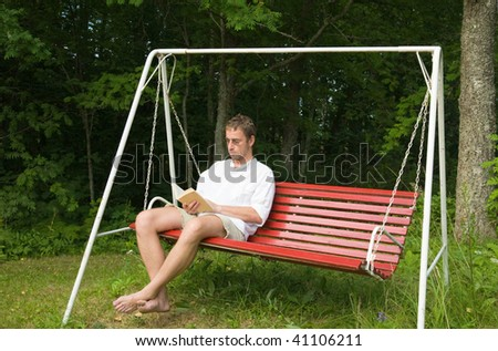 middle aged caucasian man reading a bok siting on old swing bench - old summer house situation