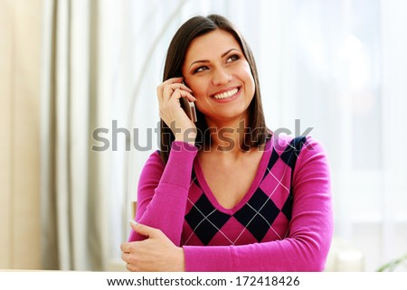 Middle-aged cheerful woman talking on the phone and looking away - stock photo