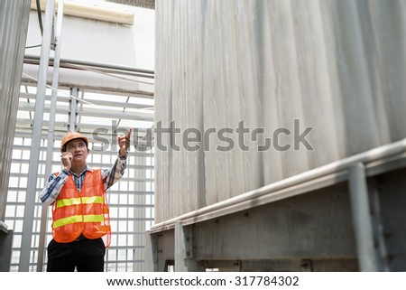 Middle-aged construction worker using portable radio transmitter to direct his colleagues - stock photo
