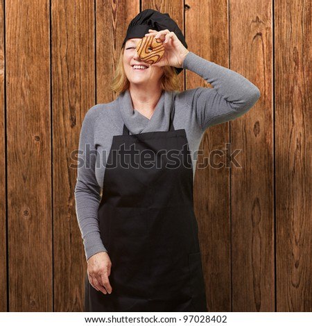 Middle aged cook woman looking through a donut against a wooden wall - stock photo