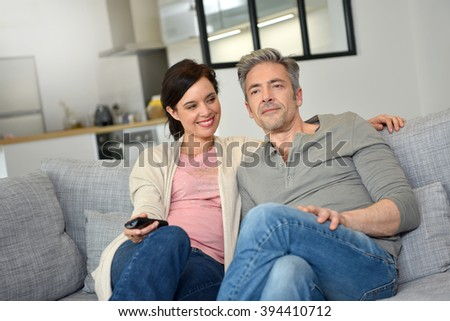Middle-aged couple at home watching television
