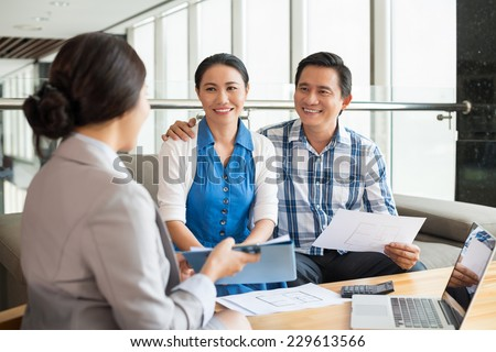 Middle-aged couple at the meeting with real estate agent - stock photo