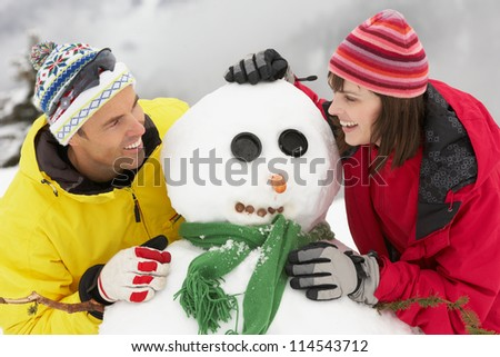 Middle Aged Couple Building Snowman On Ski Holiday In Mountains - stock photo