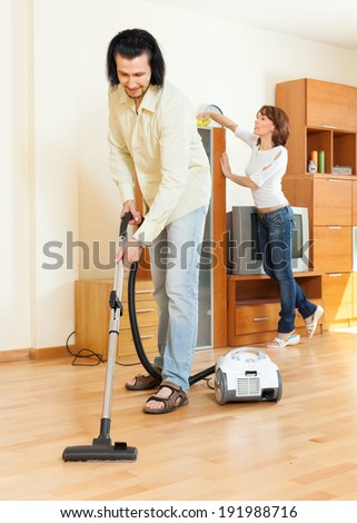 middle-aged couple cleaning with vacuum cleaner in home - stock photo