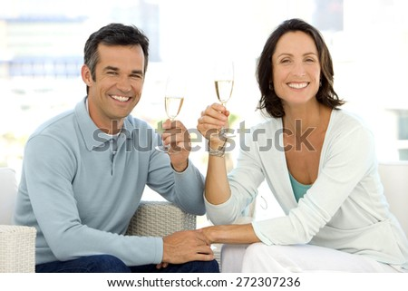 Middle aged couple drinking champagne - stock photo