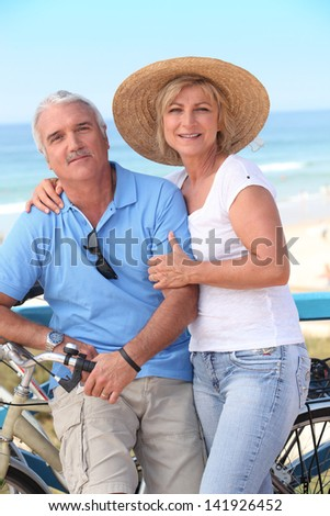 Middle-aged couple enjoying bike ride by the sea - stock photo