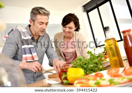 Middle-aged couple having fun cooking together - stock photo