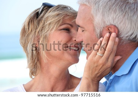 Middle aged couple kissing at the beach. - stock photo