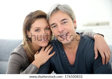 Middle-aged couple relaxing on sofa at home - stock photo