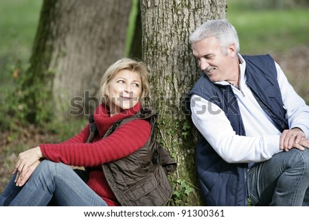 Middle-aged couple sat by tree - stock photo
