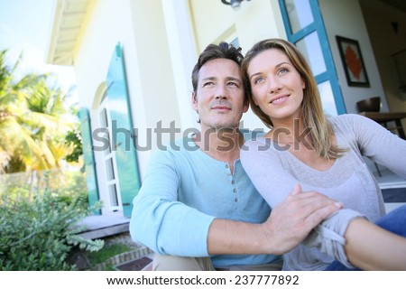 Middle-aged couple sitting on house front door - stock photo