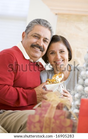 Middle Aged Couple Sitting On Sofa Holding Christmas Present - stock photo