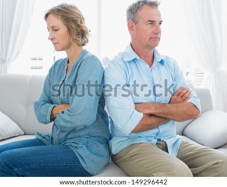 Middle aged couple sitting on the couch not speaking after a fight at home in the living room - stock photo