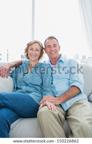 Middle aged couple sitting on the couch smiling at camera at home in the living room - stock photo
