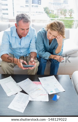 Middle aged couple sitting on their couch paying their bills at home in the living room - stock photo