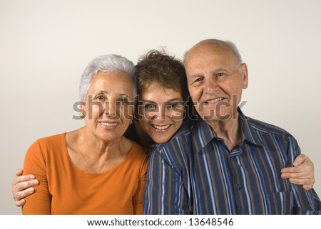 Middle aged daughter embracing her senior parents - stock photo