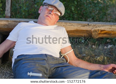 Middle-aged drug addict in a trendy cap and glasses lying slumped against a park bench in the sunshine with a rope around his arm from shooting up drugs such as cocaine or heroin - stock photo