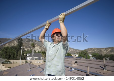 Middle aged engineer holding metallic pole on rooftop against clear blue sky