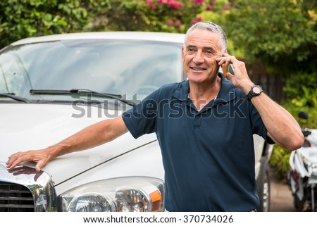 Middle aged entrepreneur speaking on mobile phone, next to his truck, closing a deal.