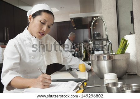 Middle aged female chef writing on clipboard with colleague working in background - stock photo