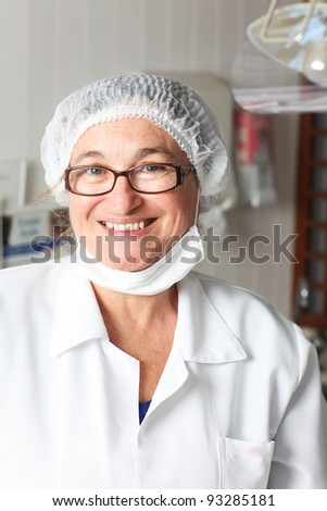 Middle aged female dentist smiling - stock photo