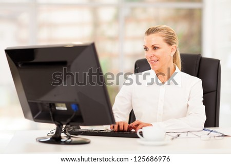 middle aged female office worker working on computer - stock photo