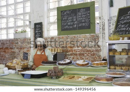 Middle aged female owner working at cake shop - stock photo