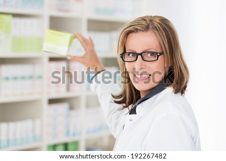 Middle-aged female pharmacist wearing glasses removing tablets off the shelf and turning to look at the camera - stock photo