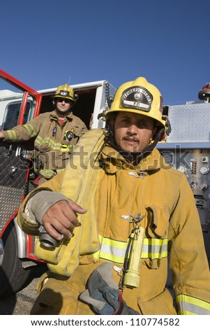 Middle aged fire worker carrying fire hose on shoulder - stock photo