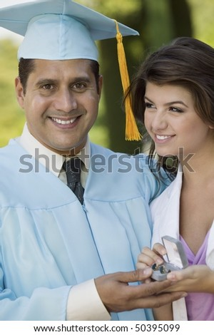 Middle-aged graduate receiving present from daughter outdoors - stock photo