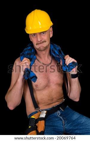 Middle aged handsome male construction worker. Studio shot, black background. - stock photo
