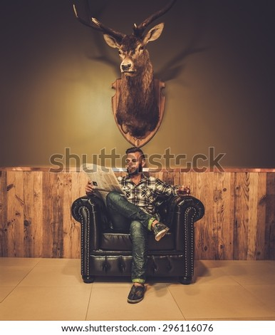 Middle-aged hipster reading newspaper on leather chair will glass of whiskey  - stock photo