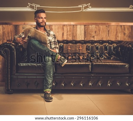 Middle-aged hipster reading newspaper on leather sofa in barber shop - stock photo