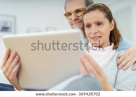 Middle-aged husband and wife using a tablet computer as they relax together on a sofa smiling as they read an e-book or catch up on social media - stock photo