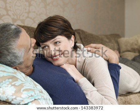 Middle aged loving couple lying together on sofa