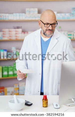 Middle-aged male pharmacist wearing a white lab coat and glasses standing in the pharmacy checking a script on his computer - stock photo