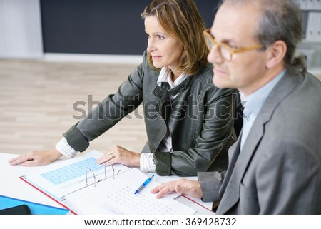 middle-aged man and woman listening to someone in a meeting