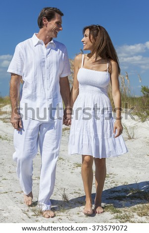 Middle aged man and woman romantic couple in white clothes walking on a deserted tropical beach with bright clear blue sky - stock photo