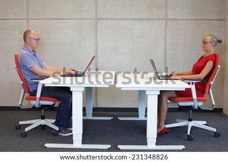 middle-aged man and young woman working in correct sitting posture with laptops  at electric height adjustable desks in office - stock photo