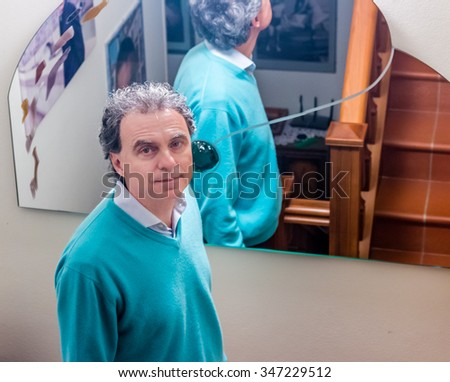 middle-aged man at home with mirror behind