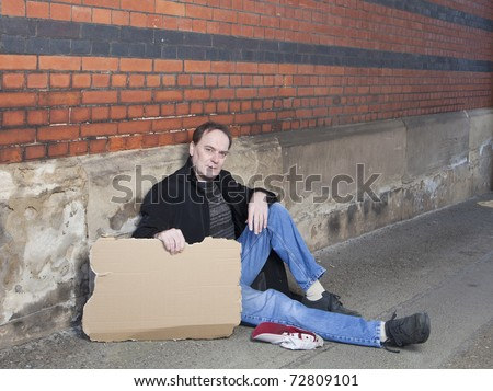 Middle aged man begging in alleyway has blank cardboard sign which is suitable for copy text