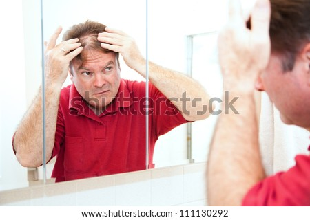 Middle aged man checking for thinning hair in the mirror. - stock photo