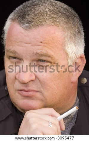 Middle aged man cigarette in hand, thinking about the errors of his ways