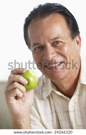 Middle Aged Man Eating Green Apple And Smiling At The Camera - stock photo