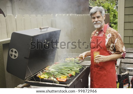 Middle-aged man grilling vegetables