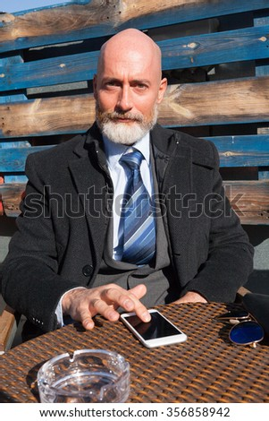 Middle-aged man , handsome and elegant working outside the office in a relaxed and sunny atmosphere - stock photo